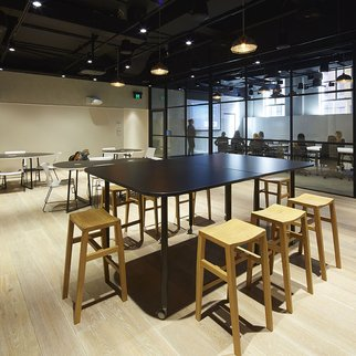 Tall Versatilis table with stools in an office setting