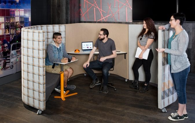 Work colleagues socialize in versatile Waltzer workstation and sofa pod