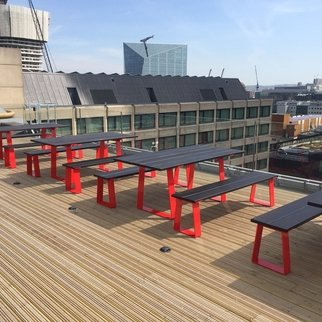 Muzo's Edge tables and benches with red leg design in rooftop setting