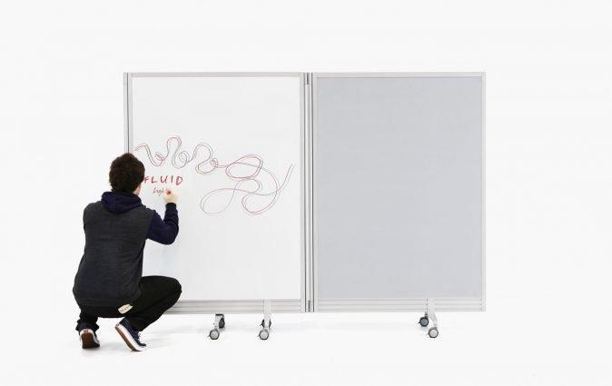 Man writes ideas on Muzo's Flow portable, folding wall