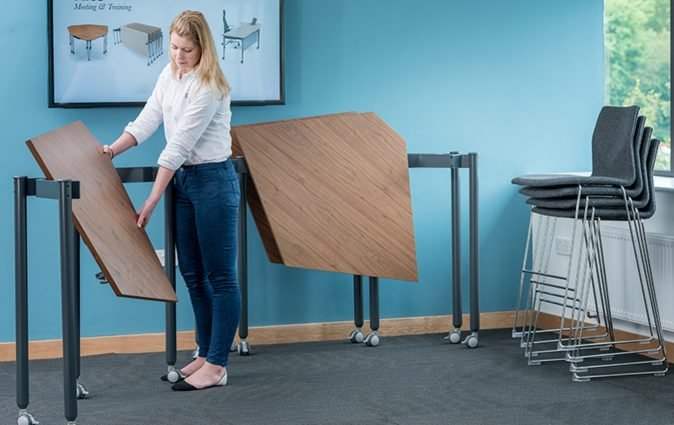 Woman folds various Kite tall, flip-top tables with ease
