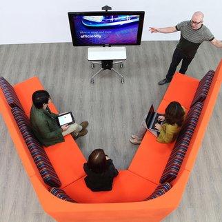 Team gathers around a Modia portable TV stand
