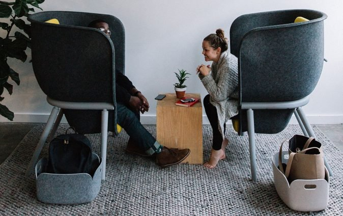 Colleagues chat from two comfortable, environmentally friendly M-Pod privacy chairs