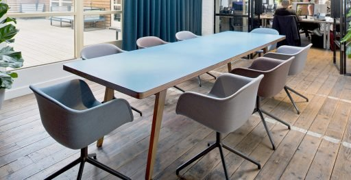 Osprey table with blue top pictured in the meeting room of busy office