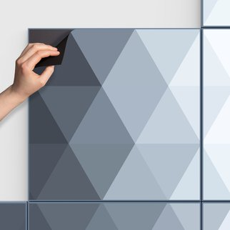 Man peels artwork from PXL magnetic wall panels