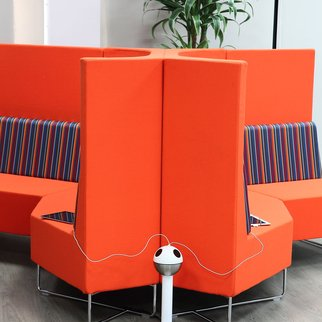 Powerball standing charging station in lobby area with brightly colored seating