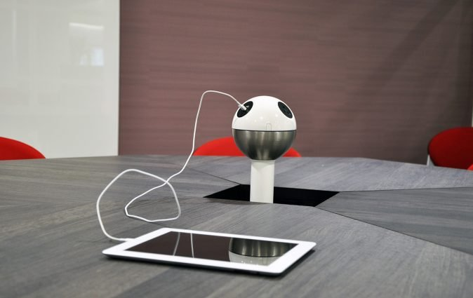 Muzo's Powerball standing charging station charges tablet at a table