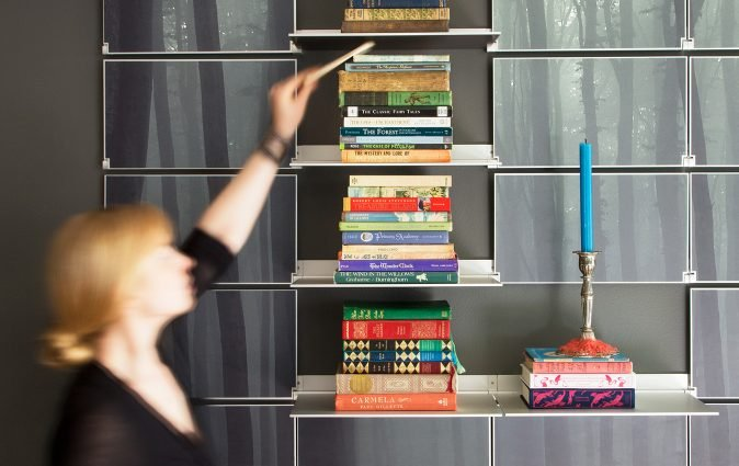 Woman places book on shelf of robust Riveli shelving system
