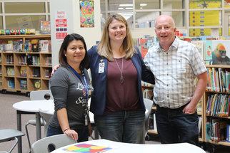 Three people pictured at library setting