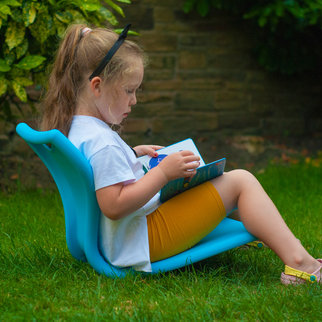 Young girl reads a book sitting on the MBob