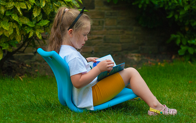 Girl reads book in her garden on an Mbob seat