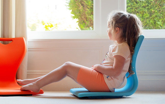 Girl relaxes in an MBob floor seat at home