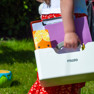Child carrying a Muzo Stashbox in the garden