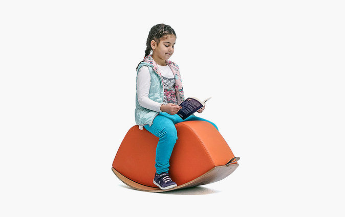 Girl reads a book while sitting on a Lips soft rocking seat