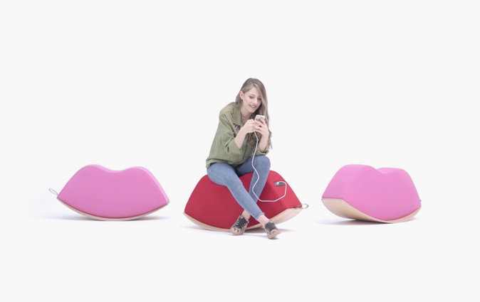 Teen charges her phone using a Lips soft rocker seat