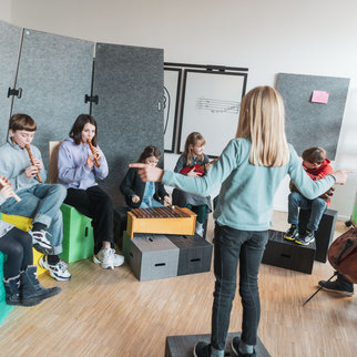 Children enjoy a music lesson sitting on Xbrick furniture