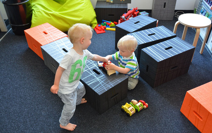 Two young children use the Xbrick for play