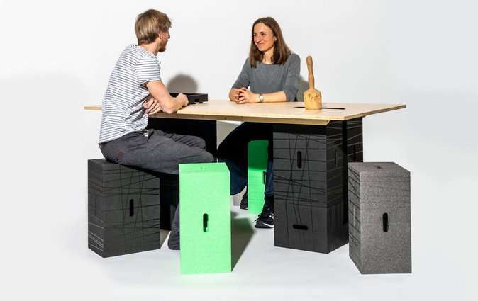 Colleagues chat at an XBrick table